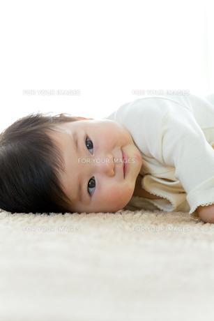 リビングに寝転んで笑う幼児の素材 [FYI01075998]
