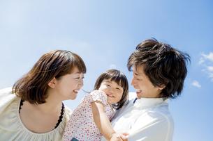 公園で娘を抱く両親の素材 [FYI01076022]