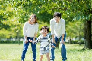 公園を走る息子を見つめる両親の素材 [FYI01076087]