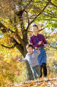紅葉の公園を走る母親と息子の素材 [FYI01076127]