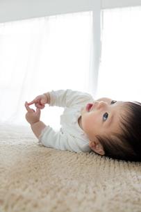 リビングに寝転んで遊ぶ幼児の素材 [FYI01076147]