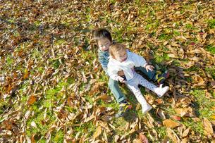 落葉の公園で遊ぶ兄と妹の素材 [FYI01076194]