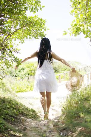 緑の小道で白いワンピースを着て手を広げる女性の後ろ姿の素材 [FYI01076545]