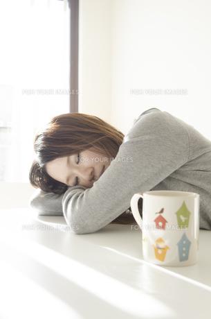 机でうたた寝をする女性とマグカップの素材 [FYI01076606]
