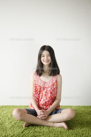 グリーンのラグの上であぐらをかいたハーフの少女の素材 [FYI01076628]