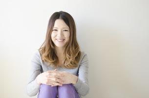体育座りをして笑顔の女性の素材 [FYI01076634]