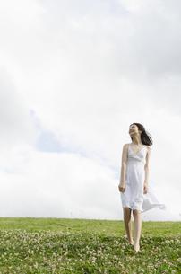 白いワンピースを着てシロツメクサの上を歩くハーフの少女の素材 [FYI01076642]