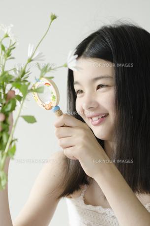 虫めがねで花を観察するハーフの少女の素材 [FYI01076647]