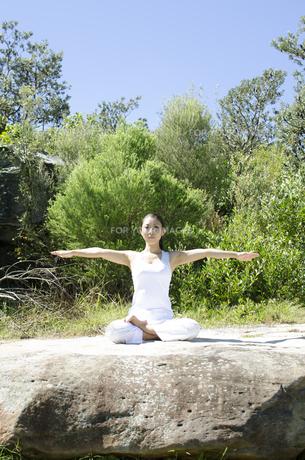 岩の上に座ってヨガポーズをする女性の素材 [FYI01076661]