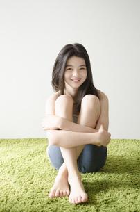 グリーンのラグの上に座ったハーフの少女の素材 [FYI01076673]