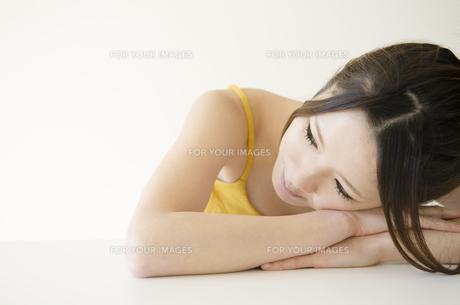 机に腕を組んで顔を乗せる女性の素材 [FYI01076674]