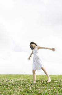 白いワンピースを着てシロツメクサの上を歩くハーフの少女の素材 [FYI01076687]