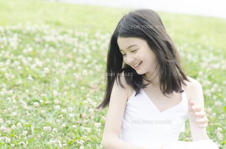 シロツメクサの上に座って笑顔のハーフの少女の素材 [FYI01076707]