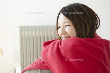 オイルヒーターの前で赤いストールに包まる女性の素材 [FYI01076709]