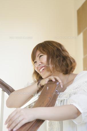 階段の手すりに持たれて笑う女性の素材 [FYI01076714]