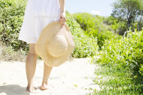 白いスカート姿で帽子を持って砂の上を歩く女性のイメージの素材 [FYI01076731]