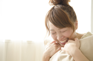 クッションを抱きしめて笑う女性の素材 [FYI01076732]