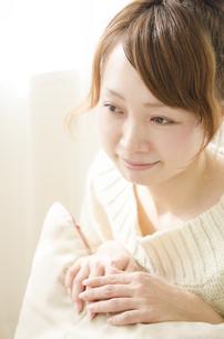クッションに手を添えて微笑む女性の素材 [FYI01076749]