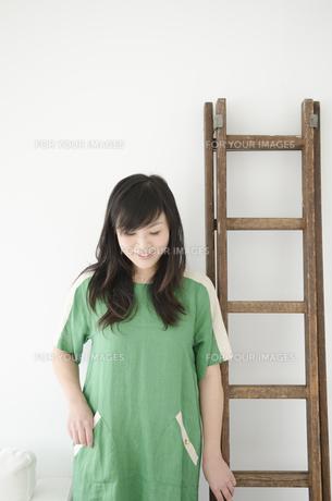 はしごの横でうつむく女性の素材 [FYI01076750]