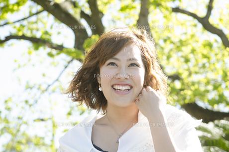 緑をバックに笑顔の女性の素材 [FYI01076752]