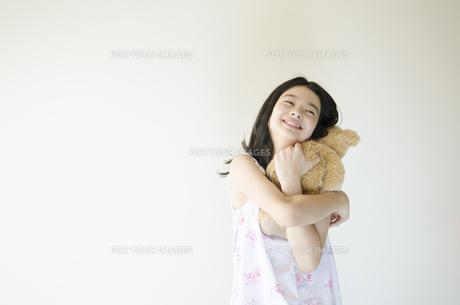 くまのぬいぐるみを抱きしめるパジャマ姿の少女の素材 [FYI01076756]