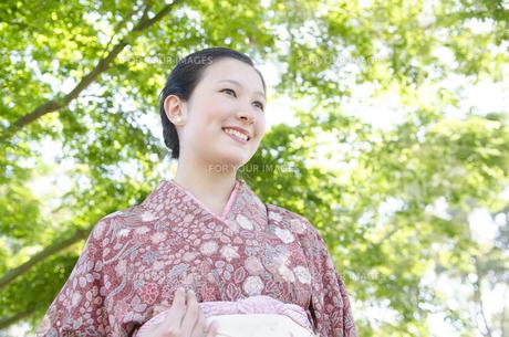新緑の中で笑う着物姿の女性の素材 [FYI01076757]
