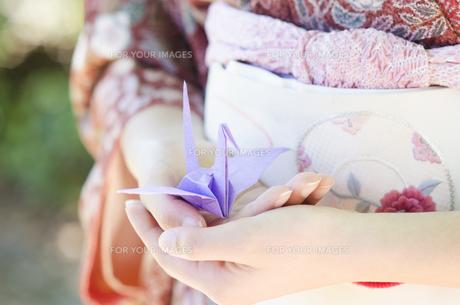 着物姿の女性の手の上に乗せた折り鶴の素材 [FYI01076761]