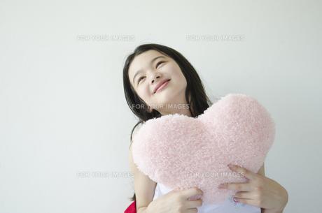 ハートのクッションを持って微笑む少女の素材 [FYI01076766]