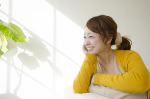 室内で頬杖を付いて微笑む女性の素材 [FYI01076782]