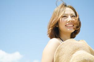 帽子を持って青空バックに笑う女性の素材 [FYI01076790]