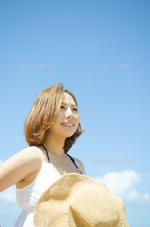 帽子を持って青空バックに笑う女性の素材 [FYI01076792]