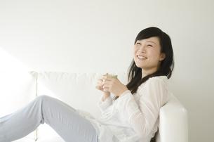 ソファに座ってリラックスする笑顔の女性の素材 [FYI01076800]