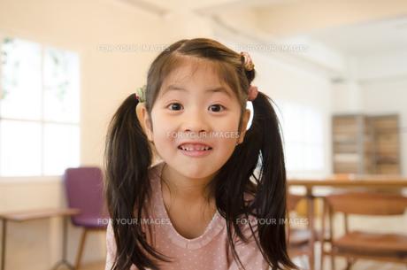 室内でおちゃめな顔をする女の子の素材 [FYI01076804]
