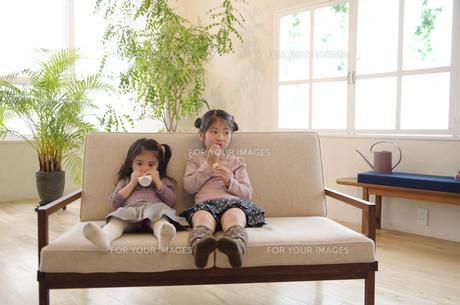 ソファでくつろぐ姉妹の素材 [FYI01076810]