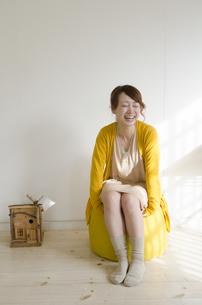 黄色いクッションに座って笑う女性の素材 [FYI01076812]
