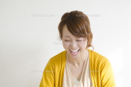 黄色いカーディガンを着て大笑いする女性の素材 [FYI01076813]