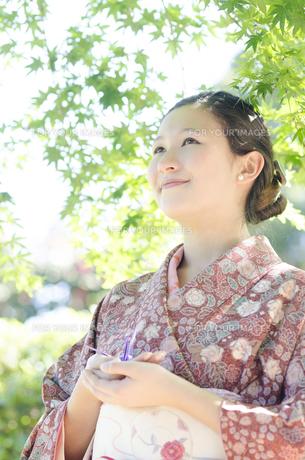 新緑のもみじをバックに微笑む着物姿の女性の素材 [FYI01076814]