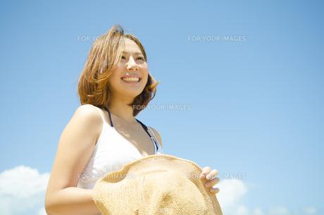 帽子を持って青空バックに笑う女性の素材 [FYI01076830]