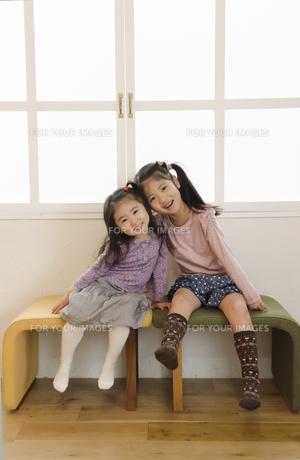 イスに座って寄り添って笑う姉妹の素材 [FYI01076839]
