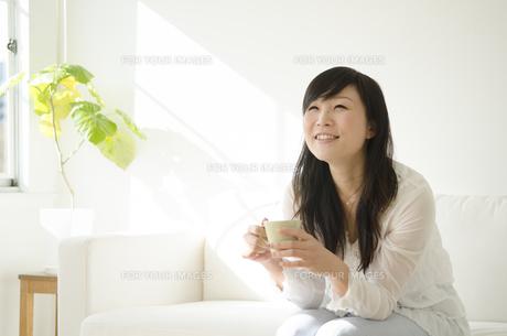ソファに座ってリラックスする女性の素材 [FYI01076849]