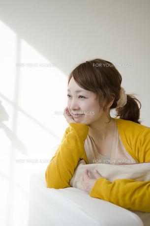 室内で頬杖を付いて微笑む女性の素材 [FYI01076861]