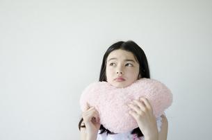 ハートのクッションを持って困った顔をする少女の素材 [FYI01076864]