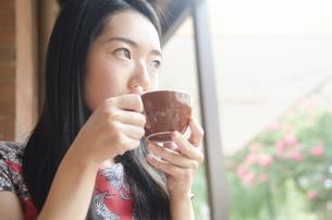 コーヒーを飲む黒髪の女性の素材 [FYI01076888]