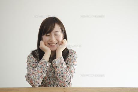 机の上で頬杖を付いて笑う女性の素材 [FYI01076889]