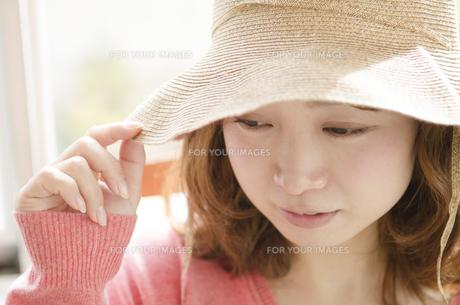 帽子をかぶってつばを触る女性の素材 [FYI01076893]