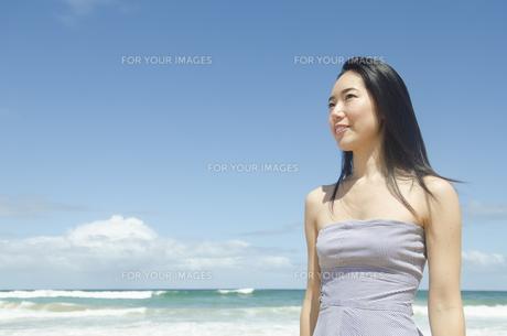 ビーチで遠くを見つめる黒髪の女性の素材 [FYI01076895]