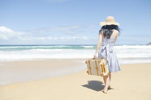 波打ち際をスーツケースを持って歩く女性の素材 [FYI01076898]