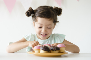 たくさんのカップケーキを見て笑うハーフの女の子の素材 [FYI01076900]