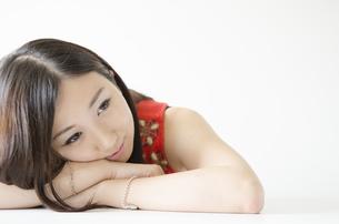 机の上に腕を組み顔を乗せる女性の素材 [FYI01076901]