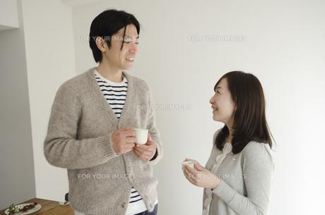 カップを持って話すカップルの素材 [FYI01076902]